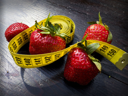 brea: The fresh Strawberry with Measuring tape on wood background in concept of healthy and diet Stock Photo