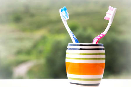Tooth brushes in glass, his and hers Stock Photo