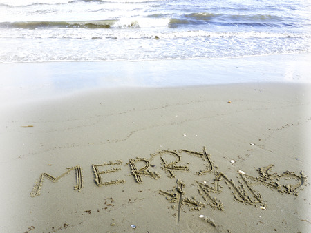 christmas tide: merry Christmas written in sand