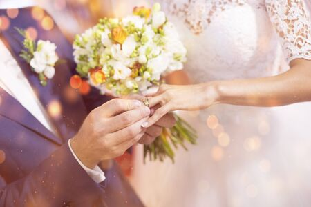 Groom puts wedding ring on brides finger, valentine background