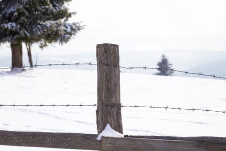 Old wooden fence in winter landscape