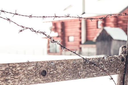 Old barbed wire fence in winter, abandoned wooden cabin