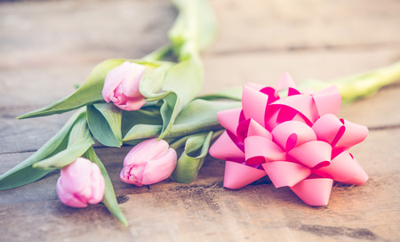 Pink tulips on rustic wooden table romantic background