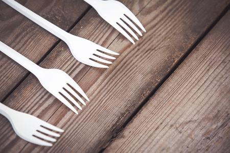 Plastic white forks on wooden background plastic free concept 版權商用圖片