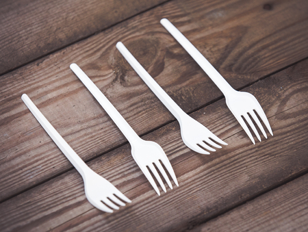 Plastic white forks on wooden background plastic free concept Stock Photo