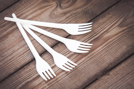 Plastic white forks on wooden background plastic free concept Imagens