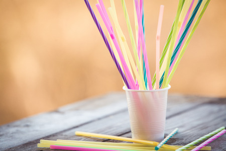 Plastic straws on wooden background plastic free concept
