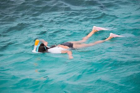 Snorkeling tourist in clear blue water paradise