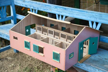 Wooden doll house on a rustic blue bench