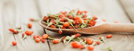 Ripe goji berries on wooden background