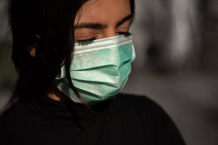 tired woman with protective fase mask - covid-19 corona crisis concept picture