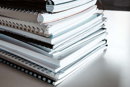 Stack of reports lies on a desk ready for review