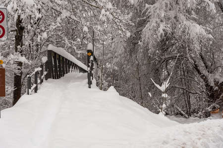 Snow covered pedestrian bridge over river after heavy snowfall