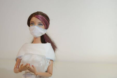 Doll with face mask and hospital supplies  closeup on white background. Illness, virus and quarantine concept.