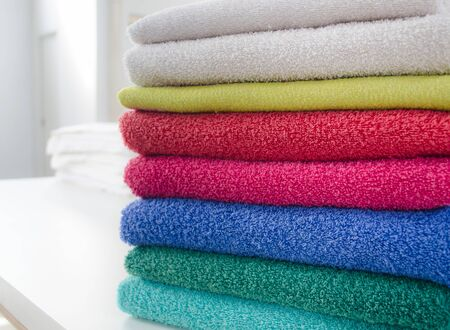 Stack of colorful and soft towels on white table. Cleaning and laundry service concept. Stock Photo