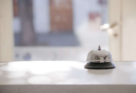 Vintage bell on a white wooden counter. Service and public attention concept.