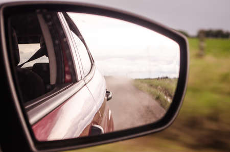 Rearview mirror reflection of a car on a dusty road in the countryside with motion blur. Speed and travel concept.