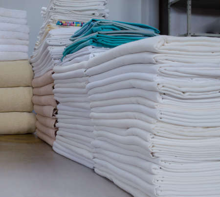 Stack of folded clean cloths in an industrial laundry. Cleaning service for institutions, hotels, hospitals and clinics. 写真素材