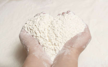 a handful of flour in the shape of a heart made as background photo