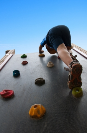 climbing wall: child climbs up the wall in the park