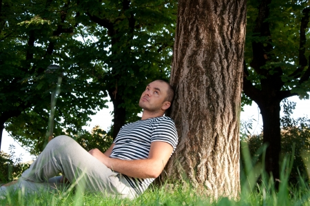 man sit: man sitting under a tree in the park