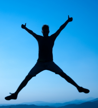 persona saltando: silueta del hombre joven que salta sobre un fondo de cielo azul Foto de archivo