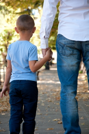 kids holding hands: father and son walking the park Stock Photo