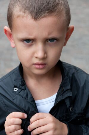 sullen: resentful a little boy of five years outside