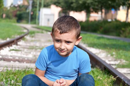 lonely little boy sitting on a rails Stock Photo - 16064787