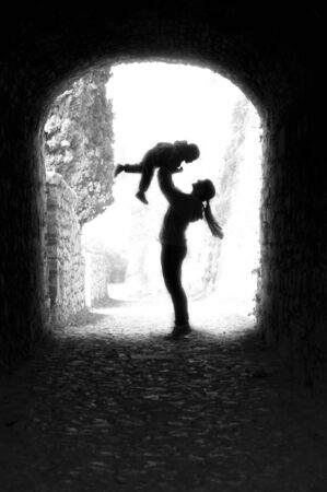 mother keeps child in her arms, silhouette black and white Stock Photo