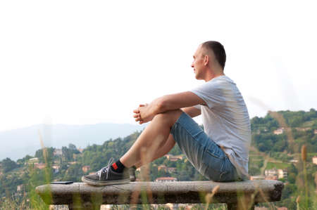 young man sitting on a bench and admire the city views
