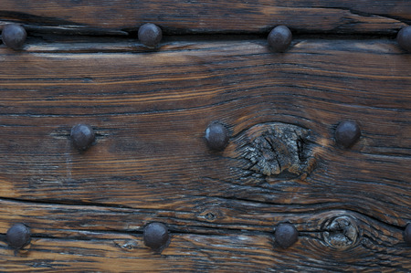 part of an ancient wooden door with hammered huge nails Stock Photo
