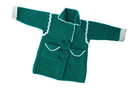 trabajo manual: jersey de punto para el niño del trabajo hecho a mano. suéter caliente con un patrón. Aislar en blanco. Foto de archivo