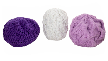 knitten: Knitted winter caps on a white background.