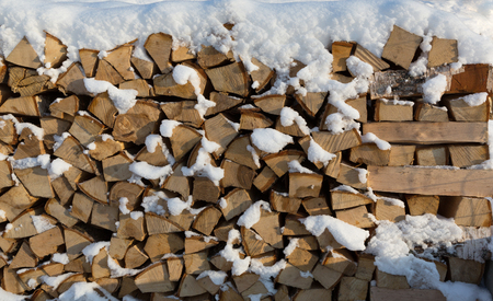 Firewood put. Chipped firewood. Firewood covered with snow. Stock Photo