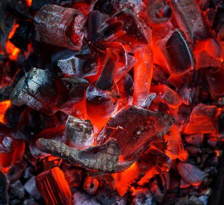 Burning coal. Glowing embers smoldering. Fire place with glowing coal. Live coal burning. Background. Close-Up.