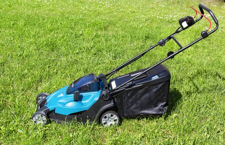 Lawn mower on green grass. Mower grass equipment, mowing gardener care work tool. Electeic Machine for cutting lawns.