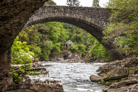 Small stone house at the river in the forest of Scotland, view under stone bridge photo