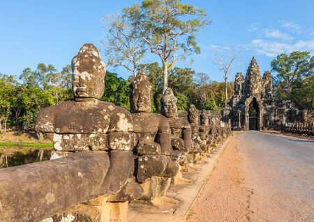 Bridge and road through the South Gate to Angkor Thom and the faces of stone giants guarding the entrance, Siem Reap, Cambodia.