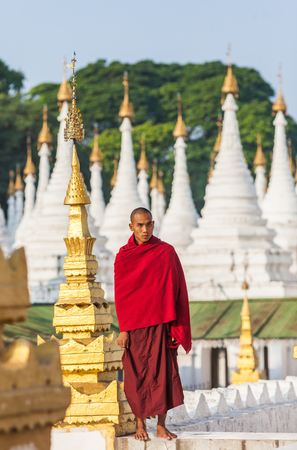 Mandalay, Myanma- December 13, 2015. Buddhist young monk stands in background Sandamuni Pagoda stupas tops on December 13, 2015 in Mandalay, Myanmar.