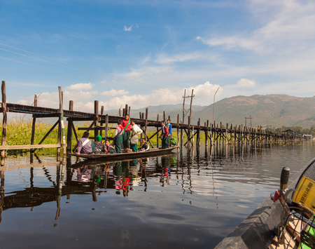 Inle Lake. Myanmar-December 21, 2015. Group of burmese school children on bamboo boat coming back from school and stopped next to the bridge at Mine Thauk village on December 21, 2015 at Inle Lake in Myanmar.