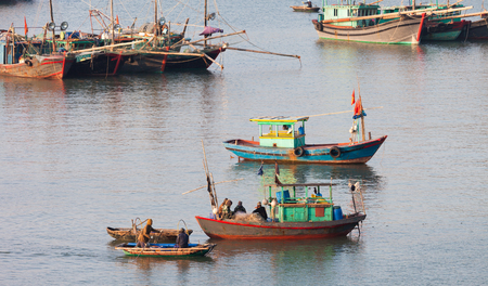 Cat Ba, Vietnam-December 19, 2013. Fishing boats and fishermen, it is common life scene in fishing harbour pier on December 19, 2013 at Cat Ba island in Ha Long Bay of North Vietnam.