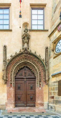 Prague, Czech Republic. Late Gothic door in the house adjacent to the tower serves as the main entrance to the Old Town Hall at the square and it is one of the citys most visited monuments.