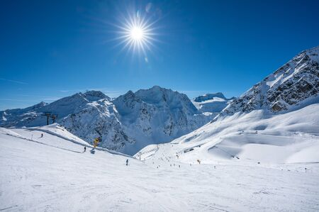 Austria, panorama of Mountain Range, winter Landscape with blue sky, sunshine and skiing slopes