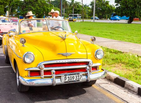 Havana, Cuba-October 07, 2016. Iconic, yellow, vintage, old American Chevrolet, used as taxi for tourist, parked and on the street of Old Havana. 報道画像