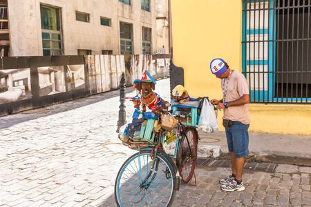 Havana, Cuba-October 07, 2016. Man at historical part of Old Havana with two dachshund breed dogs on the bicycle, dressed in colorful outfit of cuban flag to attract tourist.