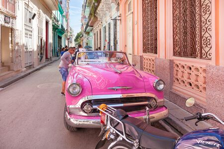 Havana, Cuba-October 07, 2016. Authentic, narrow street with old colonial buildings, classic, old style American cars and local people at every day life on October 07 2016, at old part of Havana City.