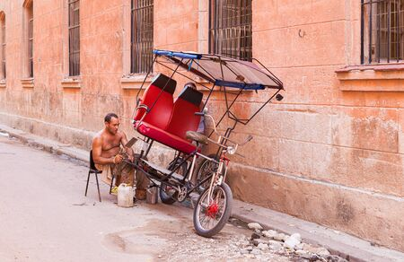 Havana, Cuba-October 07, 2016. Unindentified cuban man repaires his threecycle, used as transportaition for tourist, on October 07 2016 at street of old part of Havana City.