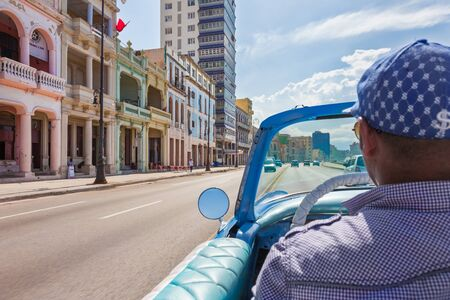 Havana, Cuba-October 07, 2016. Taxi driver driving with classic, vintage, old American car and popular tourist transportation on the Malecon street on October 07 2016, at old part of Havana City.