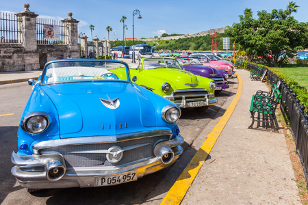 Cuba, Havana. Old classic American cars, used as Taxi, parked next to popular tourist attractions. 報道画像